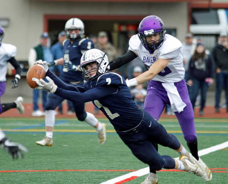PMG PHOTO: WADE EVANSON - Banks' Jarred Evans dives for a ball during the Braves' state quarterfinal playoff game against Baker Saturday, Nov. 16, at Hare Field in Hillsboro.