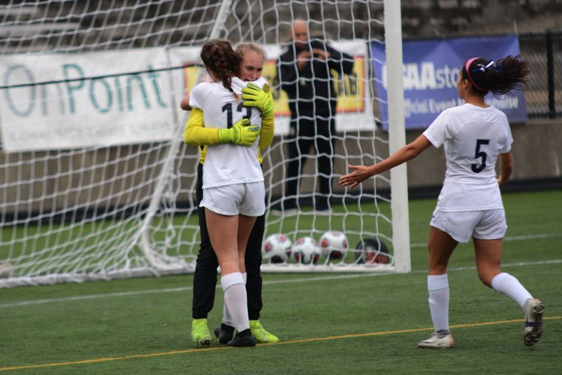 PMG PHOTO: DEREK WILEY - Wilsonville sophomore Karina Borgen, No. 13, and senior Araxi Tejada-Martinez, No. 5, console goalkeeper Kendall Taylor after the Wildcats lose in penalty kicks.