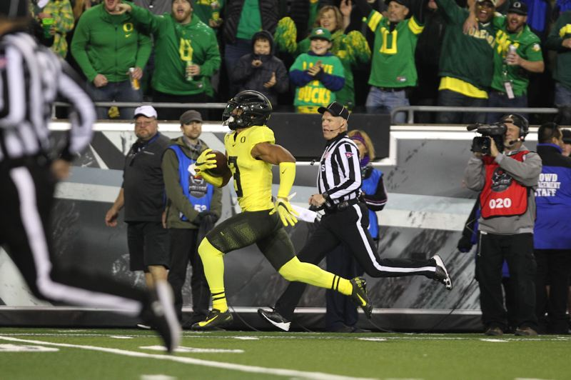 PMG PHOTO: JAIME VALDEZ - Oregon receiver Johnny Johnson III heads toward the end zone for a touchdown Saturday night against Arizona at Autzen Stadium.