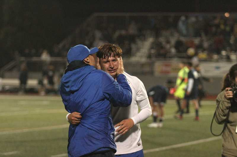PMG PHOTO: PHIL HAWKINS - Woodburn boys soccer head coach Leroy Sanchez embraces junior midfielder and 2019 Oregon West Co-Player of the Year Ricardo Hernandez following the Bulldogs 1-0 win over Stayton.