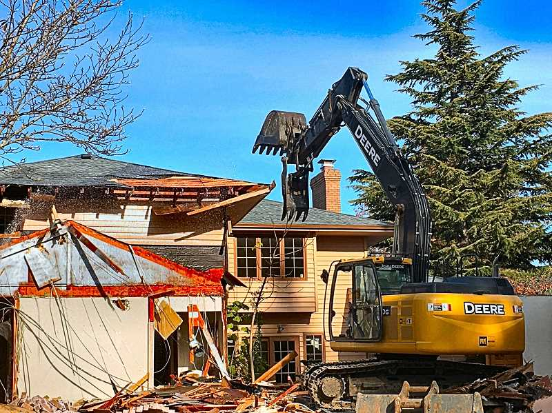 PAIGE WALLACE - Like a giant reptile being passed an hors d'oeuvre tray, the giant excavator appears to be pausing to choose the next morsel to consume. When the sprawling estate was gone, not long after this photo was taken, the builder prepared to build five new full-size houses on this large Reed neighborhood lot.