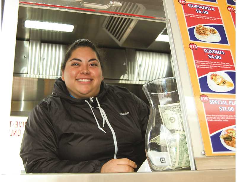 RAMONA MCCALLISTER - Yesenia Ceja greets customers with a big smile. The menu for their wide assortment of authentic Mexican dishes is on  Yesenias right.