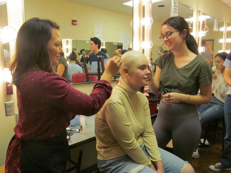 PHOTO BY ELLEN SPITALERI - Left, Laurie Lundgreen, a parent volunteer who helps with makeup for OCHS plays, shows Emma Weber, right, how to put makeup on the bald cap that Alyssa Lind wears in 'TheAddams Family.'