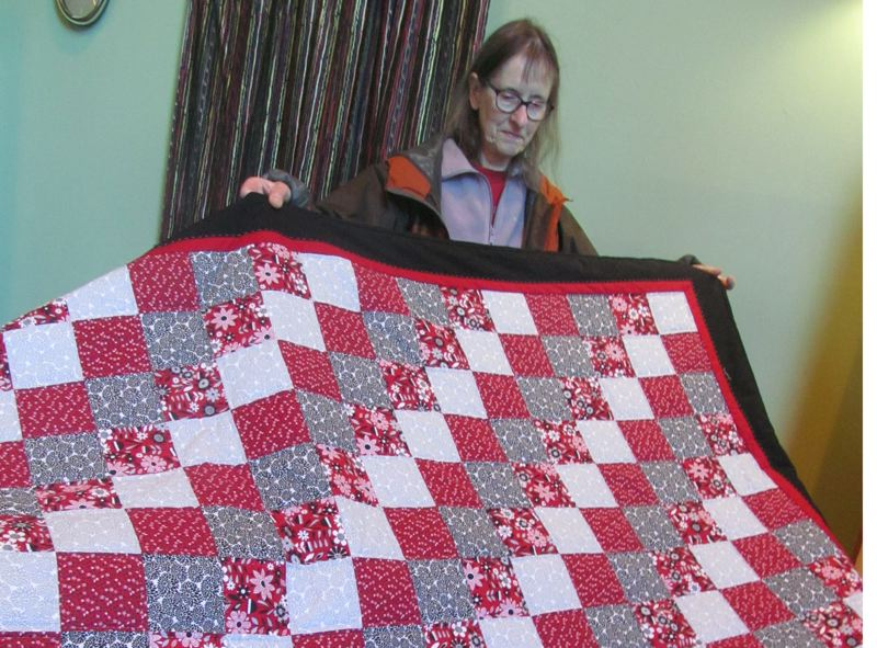 PHOTO BY ELLEN SPITALERI - Jean Herrera shows off the quilt she made with help from Clackamas United Church of Christ's Art and Spirit Circle. The quilt will be raffled off at the holiday bazaar on Nov. 23.