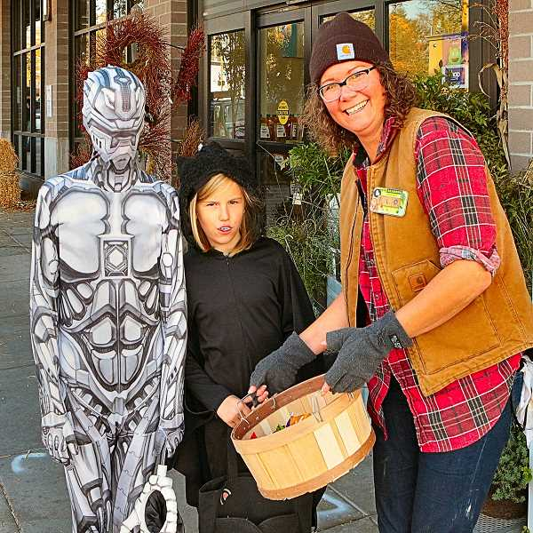 DAVID F. ASHTON - In front of the Woodstock New Seasons Market, costumed Norah and Myles Hull received treats from Flora Melhouse.