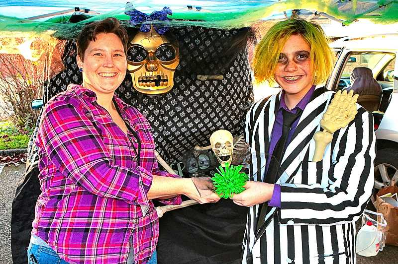 DAVID F. ASHTON - BDNA Chair Chelsea Powers awards the Best of Trunks Spook-Tacular award to the lively Beetlejuice (da Vinci Arts Middle School student Cash Fairman).