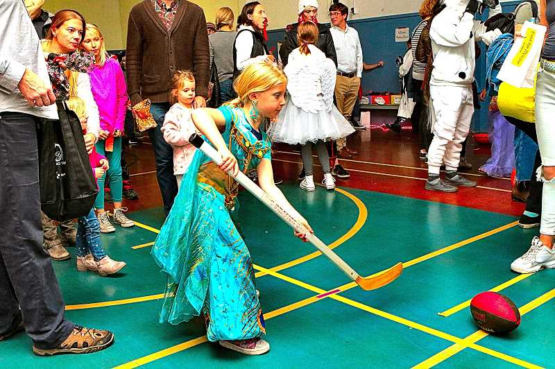 DAVID F. ASHTON - Its an odd game: Scoring a goal with a football, using a hockey stick - but Princess Jasmine, who is really Juniper Scott, scores! - during the Sellwood Community House Spooktacular.