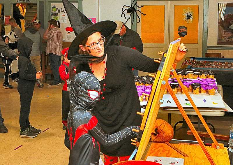 DAVID F. ASHTON - At the Sellwood Community House October 28 Spooktacular, Volunteer Julie Currin helped a Spiderman-costumed youngster to spin the Wheel of Doom. What doom will he win?
