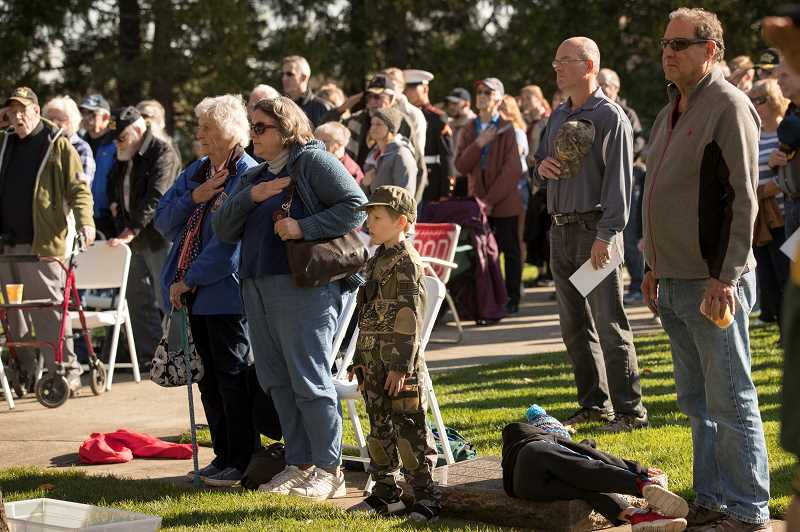 PMG PHOTO: JAIME VALDEZ - Colton Slezak, 6, of Sherwood, foreground, stands for the national anthem during a Veterans Day commemoration at the Oregon Korean War Memorial at the Town Center Park in Wilsonville.