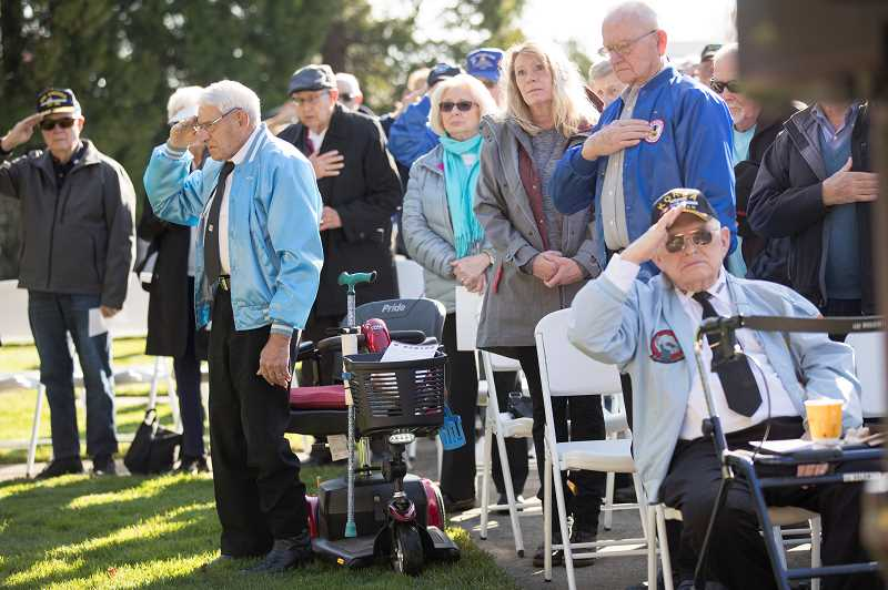 PMG PHOTO: JAIME VALDEZ - Veterans Leonard Bernhardt (blue jacket on right) and Bob Cassidy (seated) salute the American flag during the posting of colors during a Veterans Day Commemoration at the Oregon Korean War Memorial at the Town Center Park in Wilsonville.