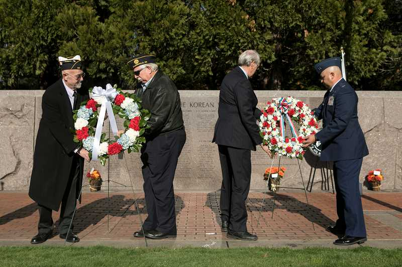 PMG PHOTO: JAIME VALDEZ - Veterans John E. Molesworth, left, and Bob Milano, Mayor Tim Knapp and veteran John Budiao place wreaths at the Oregon Korean War memorial during a Veterans Day commemoration at the Town Center Park in Wilsonville.