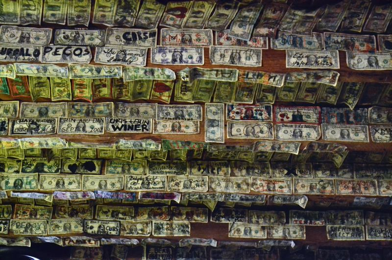 PMG PHOTO: BRITTANY ALLEN  - The tradition of signing dollars to plaster to the ceiling at Calamity Janes came about in 2004. Many are still up there to this day.
