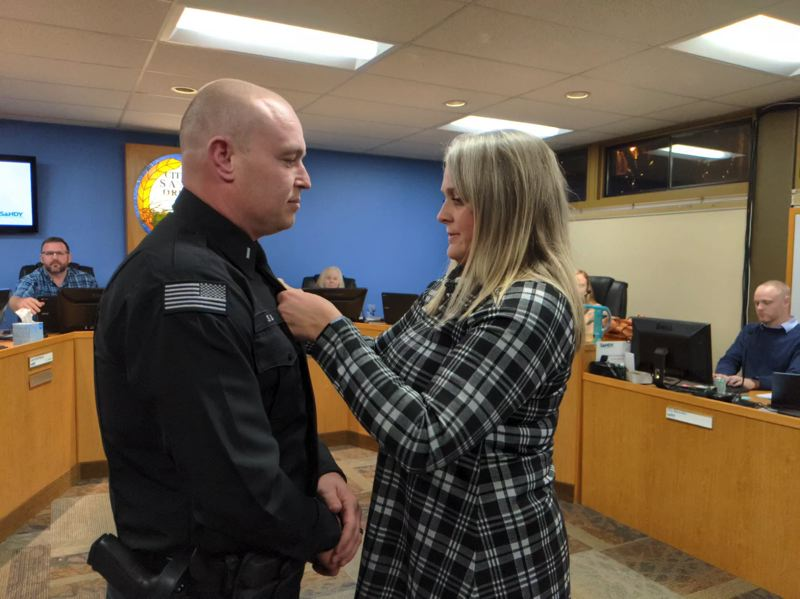 PMG PHOTO: BRITTANY ALLEN - Shawna Lundry pins new badge on Lt. Sean Lundry.