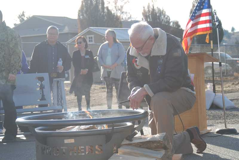 TERESA JACKSON/MADRAS PIONEER - Vietnam veteran Shawn Stanfill lights a fire to dedicate the Veterans Healing Memorial at the Jefferson County Community Center. The first two phases of the project are complete.