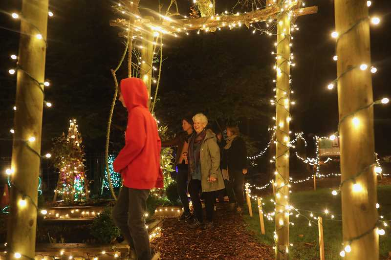 PMG PHOTO: JAIME VALDEZ - Alma Coston, right, leads family members  on a tour of Maddax Woods at the Lighting of Maddox Wood event in West Linn. The Maddax family donated the land to the city.