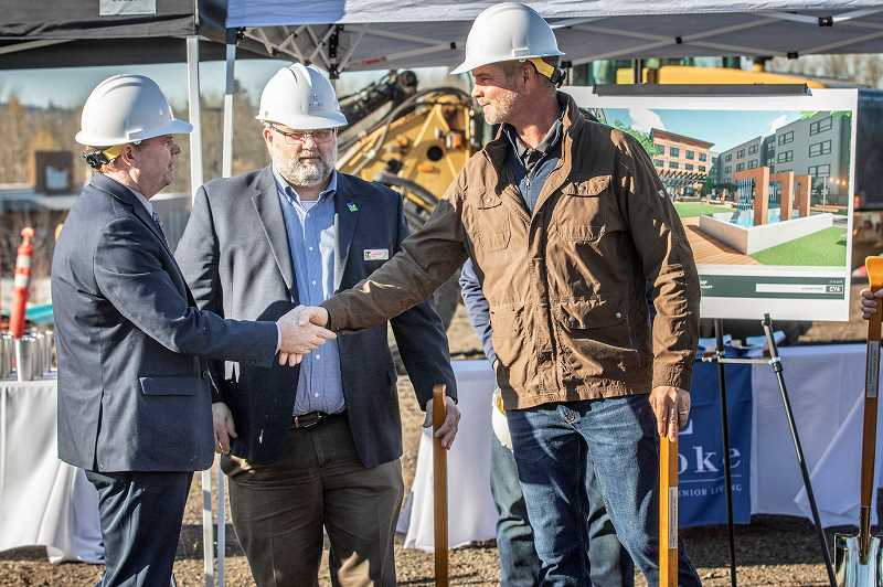 PMG PHOTO: JON HOUSE - Developer Brian Bennett, right, shakes the hand of Tigard City Councilor Tom Anderson as Tigard Mayor Jason Snider looks on during a groundbreaking ceremoney for the Evoke Senior Assisted Living Community.