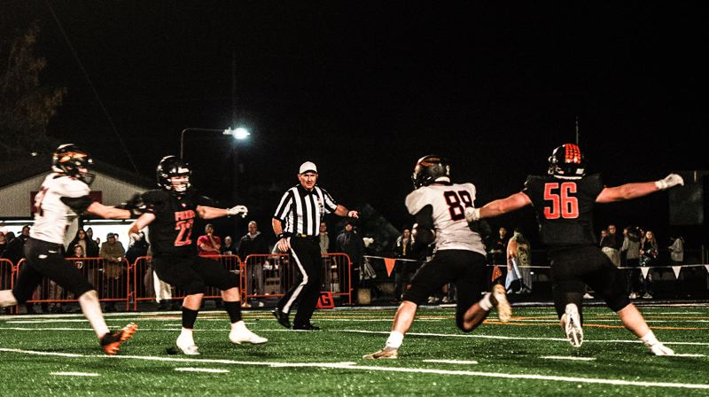 COURTESY PHOTO: JOSI WELTER - Scappoose punter Tyler Holcomb (88) finds himself cornered by Silverton's Nathan Gubbels (22) and Ethan Gubbels (56) deep in Indians territory after a snap went awry early in last week's state playoff game. Deacon Smith (21) rushes back to try to help, but the miscue leads to Silverton's first score in a 48-14 victory for the Foxes.