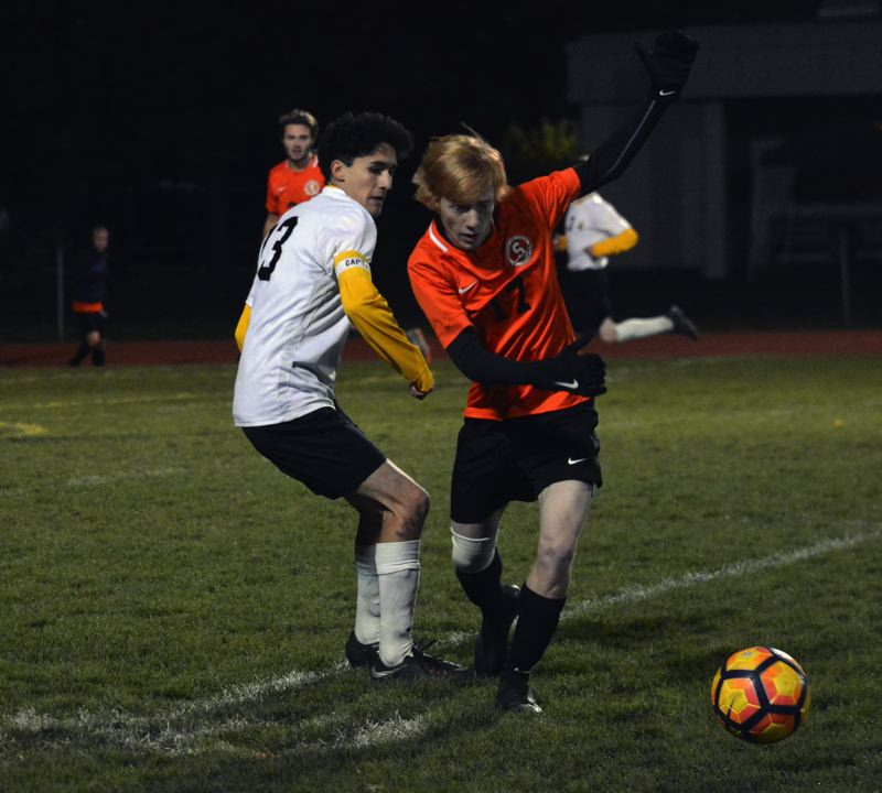 PMG PHOTO: MATT SINGLEDECKER - Scappoose's Teegan Bond (right) and St. Helens' Michael Aguilar-Rose battle for the ball.
