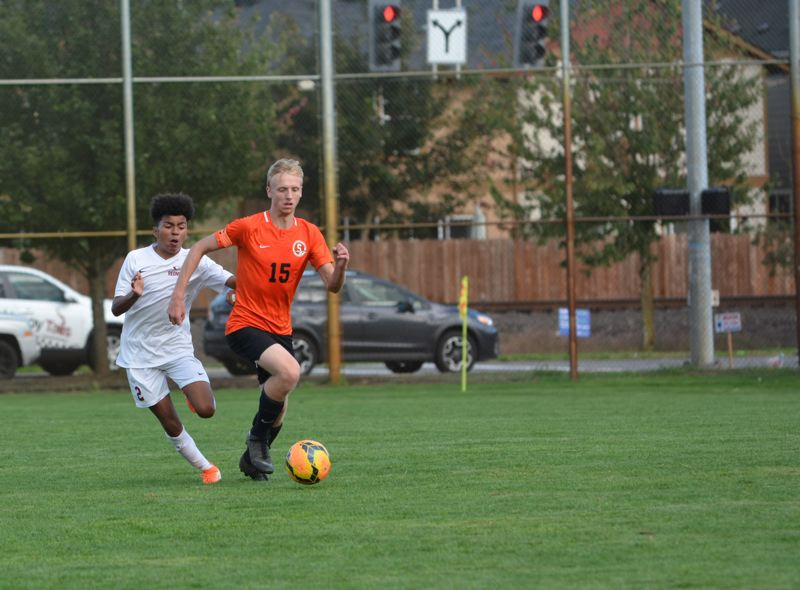 PMG PHOTO: STEVE BRANDON - Jake Boyle of Scappoose advances past a defender and through midfield.