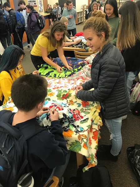 COURTESY PHOTO - High school students volunteer to put the blankets together.
