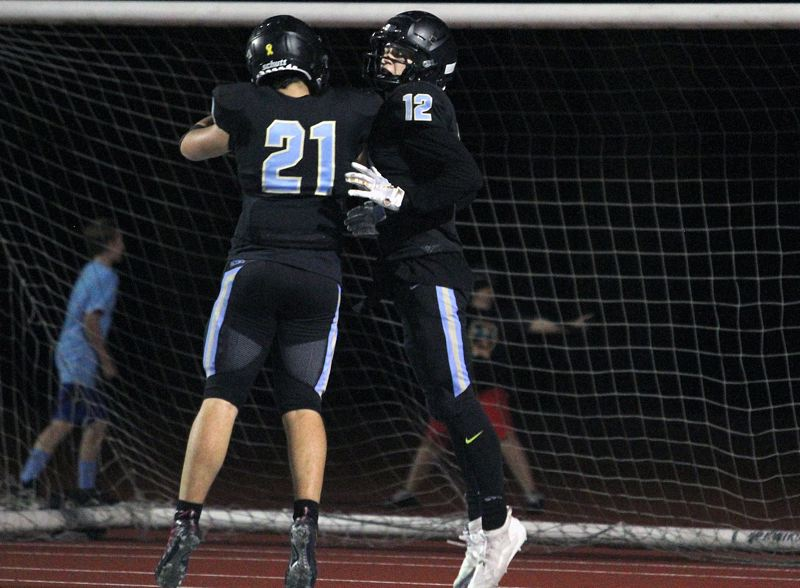 PMG PHOTO: MILES VANCE - Lakeridge senior Xander Houck (right) celebrates his second-quarter touchdown with teammate Orion Crofut during the Pacers 50-13 loss to Sherwood at Lakeridge High School Friday, Sept. 20.