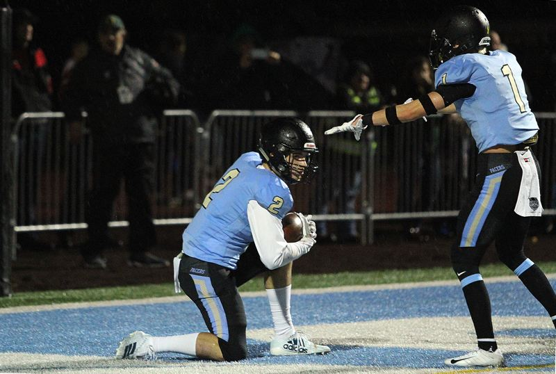 PMG PHOTO: MILES VANCE - Lakeridge's Andrew Oliver kneels down while teammate Bryson Corbin points his way after Oliver's second interception during their team's 48-27 loss to West Linn  at Lakeridge High School Friday, Sept. 27.