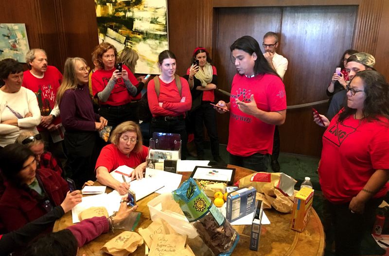 OREGON CAPITAL BUREAU: SAM STITES - Thomas Joseph (center in red shirt) speaks to Gov. Kate Brown on Chief of Staff Nik Blosser's telephone demanding she take a stance against the Jordan Cove LNG pipeline.  Joseph was among a group of protesters who occupied the governor's ceremonial office in the State Capitol Thursday, Nov. 21.