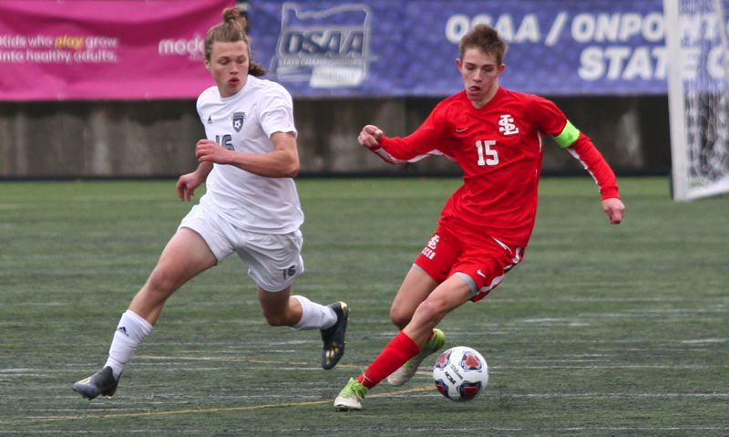 PMG PHOTO: JIM BESEDA - La Salle Prep's Wade Nichols (15) works the ball away from Wilsonville's Oliver Hardt during the second half of the OSAA Class 5A boys soccer championship final at Hillsboro Stadium.
