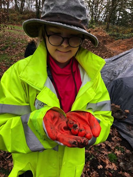 Kraxberger Middle School sixth grader Laura Wolchesky finds a snail while helping restore Gladstone Nature Park.