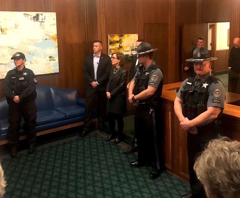(Image is Clickable Link) COURTESY PHOTO: SOUTHERN OREGON RISING TIDE - Gov. Kate Brown, flanked by security, staff and state troopers, talked with Jordan Cove protesters Thursday night, Nov. 21. Twenty-one people were arrested in a sit-in at Brown's ceremonial State Capitol office.