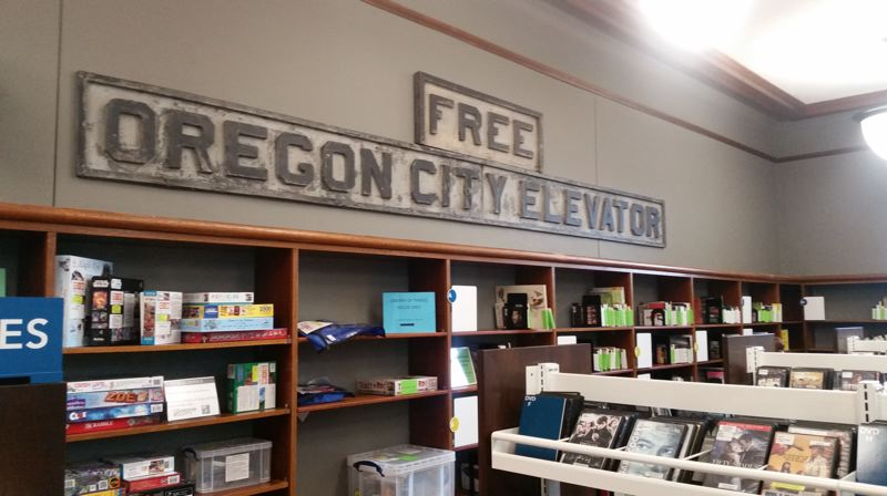 PMG PHOTO: RAYMOND RENDLEMAN - A sign that hung over the original Oregon City Municipal Elevator is now displayed as art for the holds and DVD area of the city's public library.