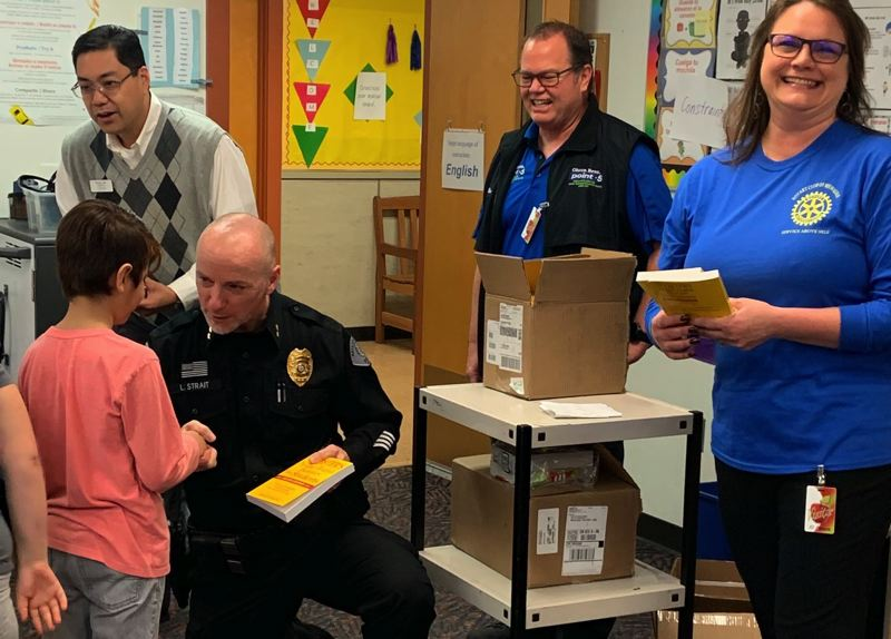 COURTESY PHOTOS - Milwaukie-El Puente elementary schoolchildren get dictionaries from Milwaukie Rotarians Steven Tam (from left), Luke Strait, Brad Olson and Tara Cunningham.
