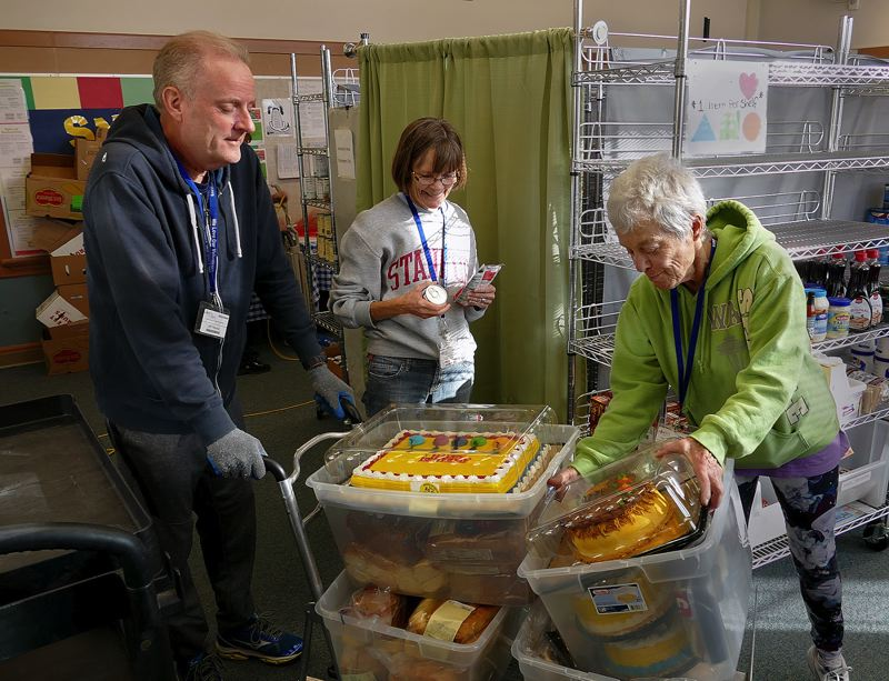 COURTESY PHOTOS - Wichita Center for Family and Community volunteers Jeff Hanna, Janet McCullough and Peggy Salo unpack cakes from the Oregon Food Bank to donate to needy families.