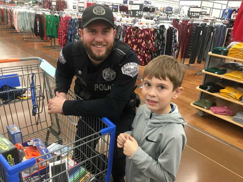 COURTESY PHOTOS - LOPD Officer Brock Rosenthal shops with a child during the Shop with a Cop event last year.
