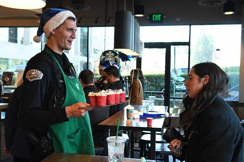 Officer Paul Valesano hands out drinks at the Coffee with a Cop event at the Meadows Road Starbucks.