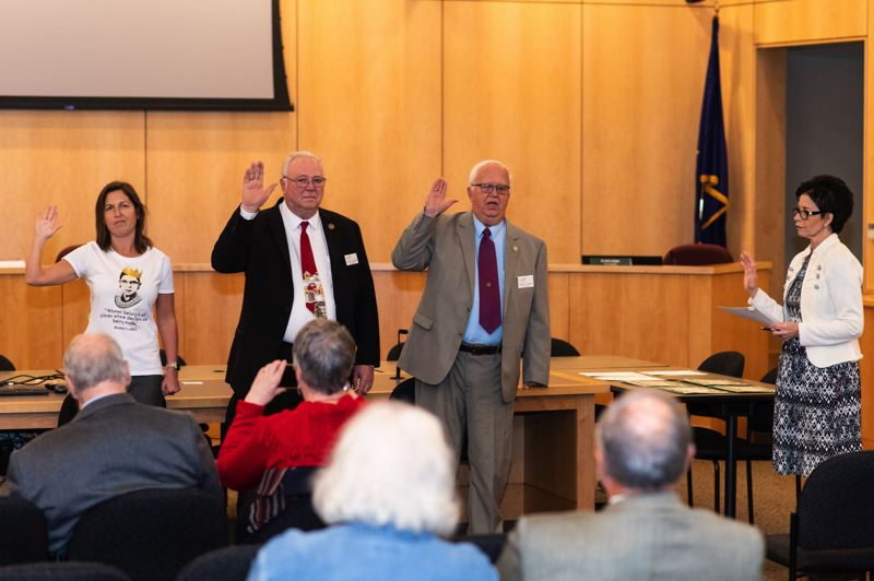 PMG PHOTO: CHRISTOPHER OERTELL - From left, Malynda Wenzl, Tom Johnston and Ron Thompson take the oath of office for new four-year terms on the Forest Grove City Council, as administered by City Recorder Anna Ruggles, far right. Johnson's death in October opened a seat on the council that must be filled by appointment.