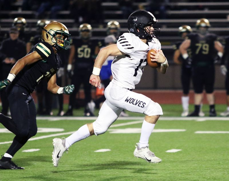 PMG PHOTO: DAN BROOD - Tualatin High School senior quarterback Blake Jackson (right) sprints into the clear ahead of Jesuit senior Kaba Haou during Friday's state playoff quarterfinal game.