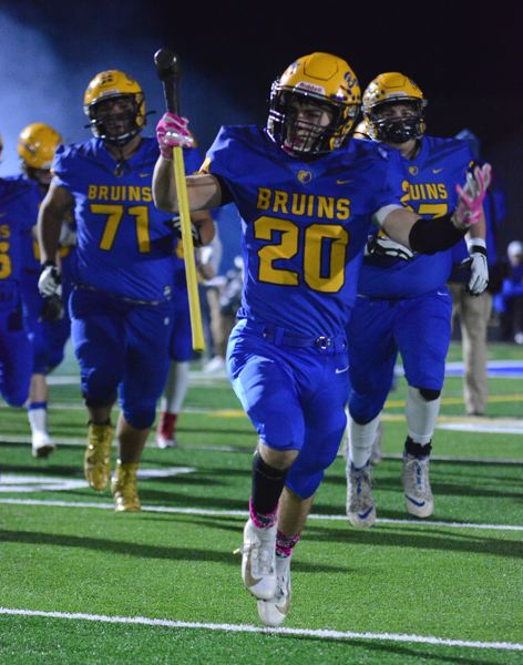 PMG PHOTO: DAVID BALL - Barlows Josh Nomie leads the Bruins onto the field to start the Bruins 20-16 quarterfinal win over Mountainside on Friday.