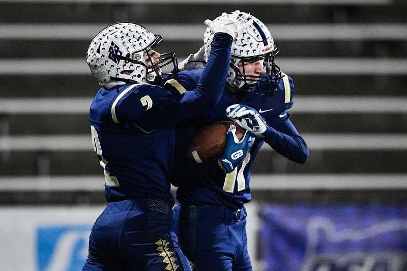 PMG PHOTO: CHRISTOPHER OERTELL - Banks' Jarred Evans (2) and Jacob Slifka (11) celebrate a touchdown during the Braves' state semifinal win over the Marist Catholic Saturday night, Nov. 23, at Hillsboro Stadium.