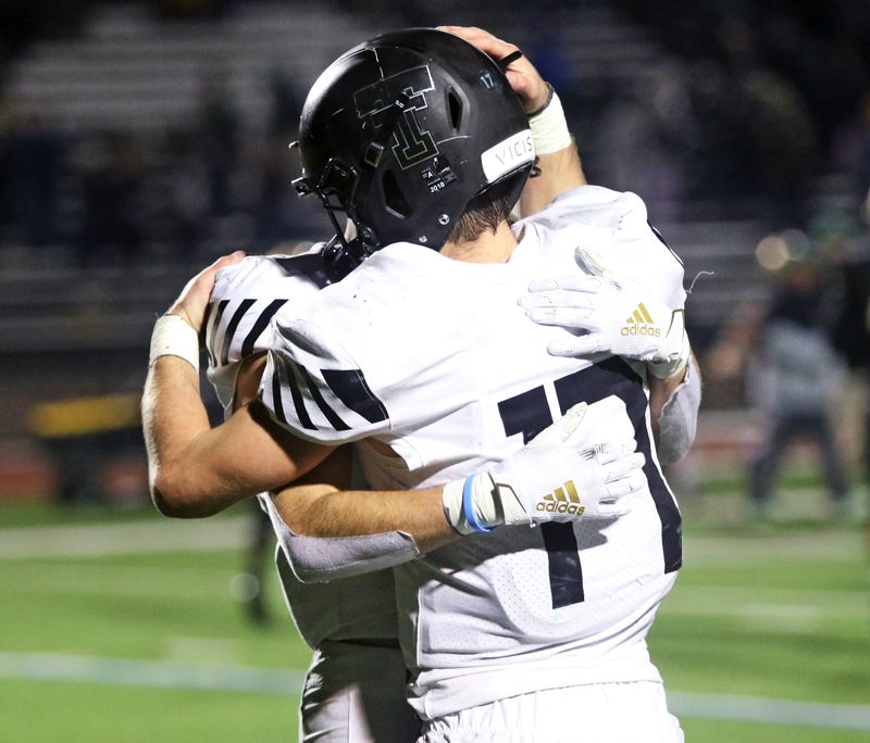 PMG PHOTO: DAN BROOD - Tualatin High School senior Blake Jackson (17) hugs senior Luke Marion following the Timberwolves' 42-28 loss at Jesuit in Friday's Class 6A state playoff quarterfinal game.