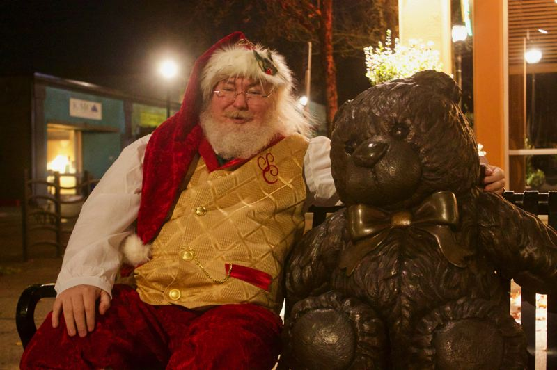 PMG PHOTO: CHRISTOPHER KEIZUR - Santa Claus takes a break with Teddy the bronze bear during one of his nightly strolls through Gresham.