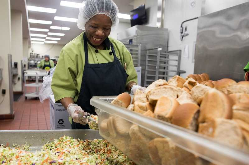 PMG PHOTO: JAIME VALDEZ - Hanh Neuman scoops coleslaw at the Meals on Wheels People headquarters in Multnomah Village. For the last 30 years, the nonprofit has been preparing Thanksgiving dinners to homebound seniors in the area.