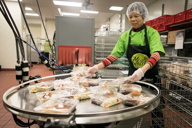 PMG PHOTO: JAIME VALDEZ - Ling Hu watches packages of prepared food travel along a conveyor belt at the Meals on Wheels People headquarters in Multnomah Village. The nonprofit plans to deliver over 2,000 hot meals to seniors on Thanksgiving.