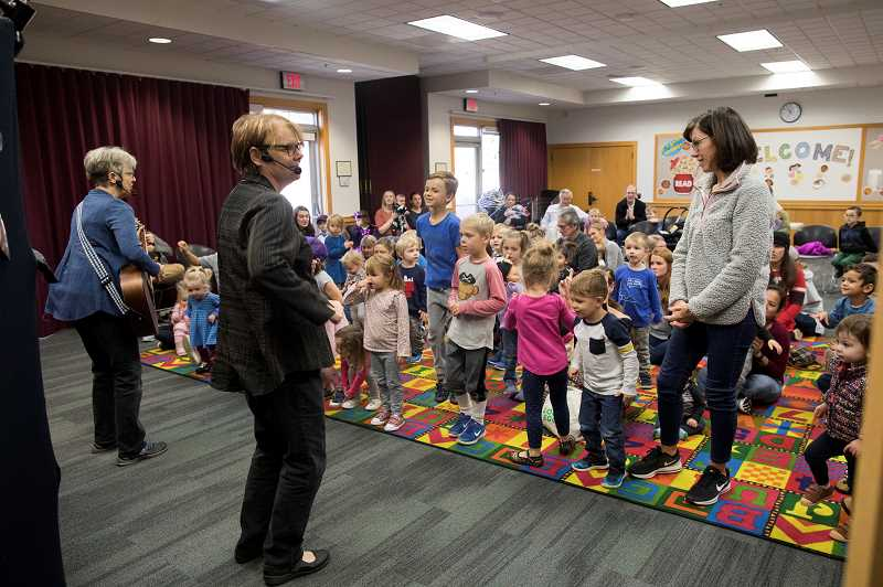 PMG PHOTO: JAIME VALDEZ - Terri Workman, left, and Jo Caisse lead children in a song during storytime at the Wilsonville Library.