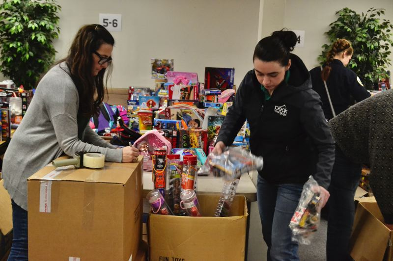 PMG FILE PHOTO  - Firefighters, students and community members help the Sandy Kiwanis Club assemble toy bags for the annual Christmas Basket Program.