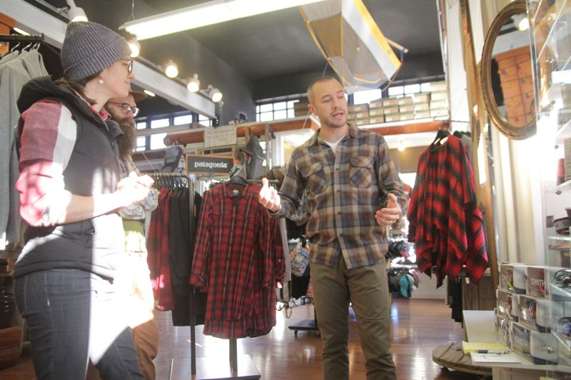 COURTESY PHOTO: RONALD BOND/LA GRANDE OBSERVER - Jim Whitbeck, right, discusses a display Friday with Carolyn Brandt and Eric Lincoln at his business Blue Mountain Outfitters in La Grande. The business is going on 5 1/2 years of growth.