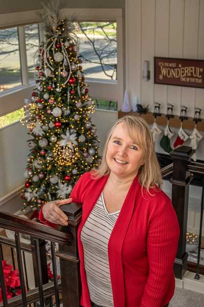 Dawna Burke poses on the landing of the staircase, which gives a great view of the holiday decor in the rooms below.