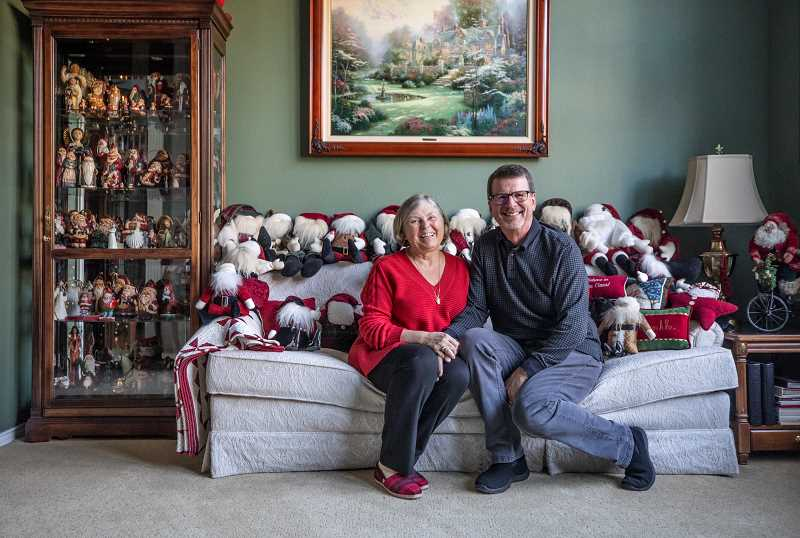 Sharon and Tom Loun sit with a group of Santas in their living room on the Holiday Home Tour.