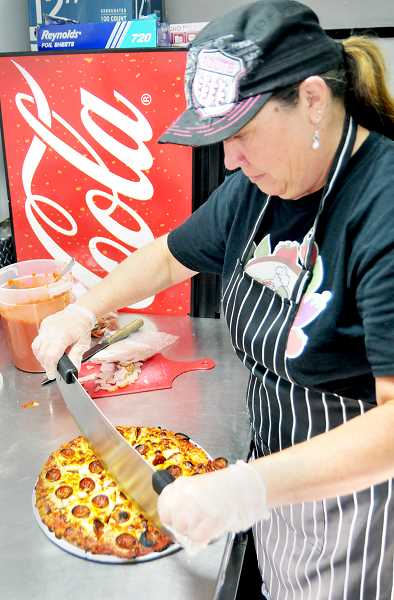GRAPHIC PHOTO: GARY ALLEN - Laura Clendenin prepares a pizza for a customer last week.