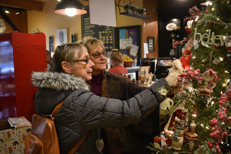 PMG PHOTO: SHANNON O. WELLS - Newport resident Dianne Eckstein, (left) and Pam Huston of Boring check out a Christmas tree display at Celebrate Me Home/Rustic With a Twist, one of the uniquely festive locally owned shops that is well stocked and prepared for Small Business Saturday and the holiday shopping season it initiates.